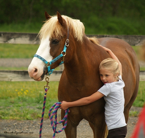 A young participant gives her pony a hug during the ground phase of the natural horsemanship clinic.